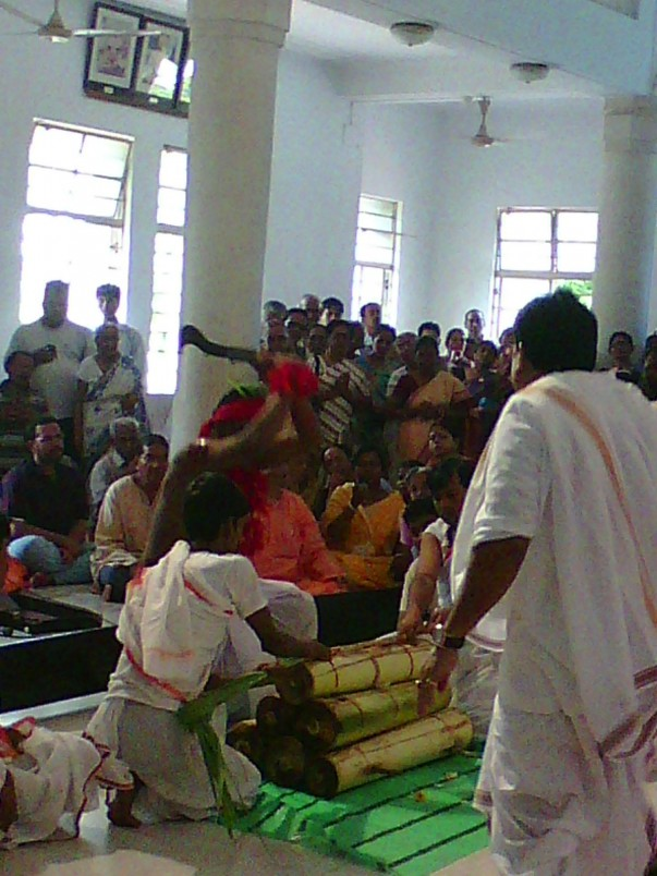 A falchion in hand, the man splits a  bundle of sugarcane, gourd and bananas, a symbolic killing of evil