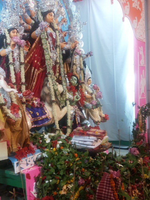 The idol of the Goddess, after she has received offerings of clothes and flowers from her devotees