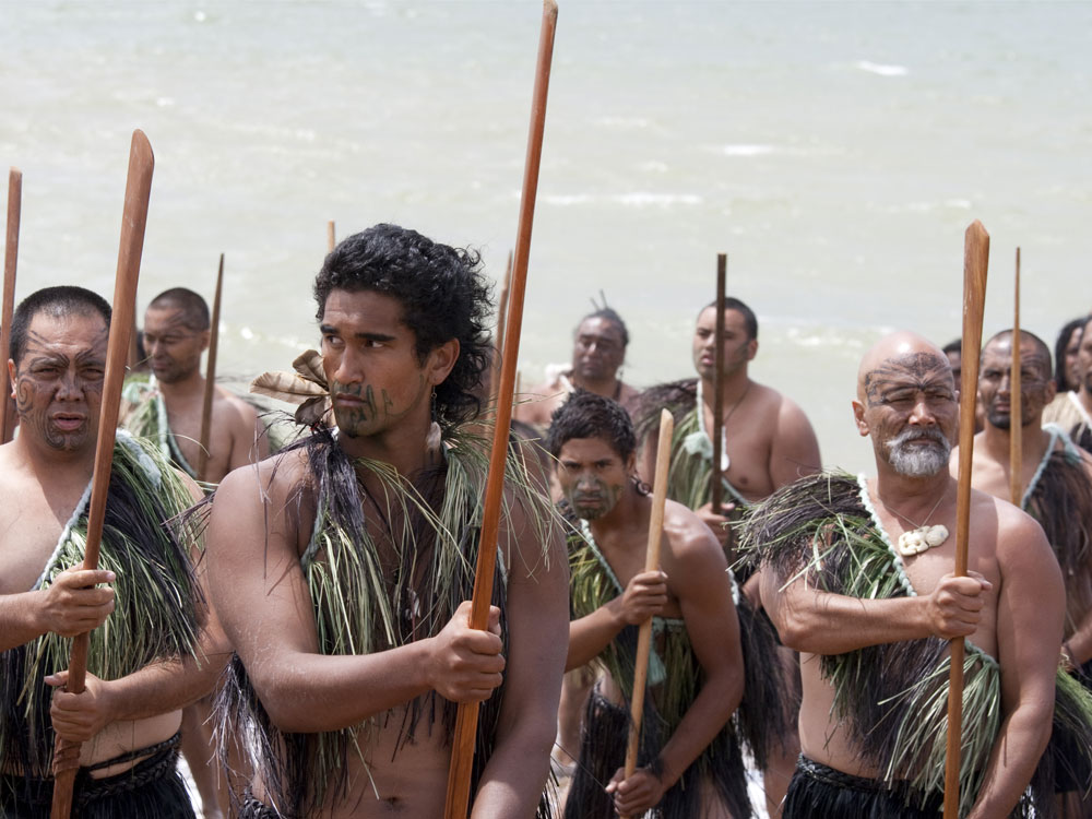 Maori warriors with taiahas at a Haka on Waitangi Day celebration.