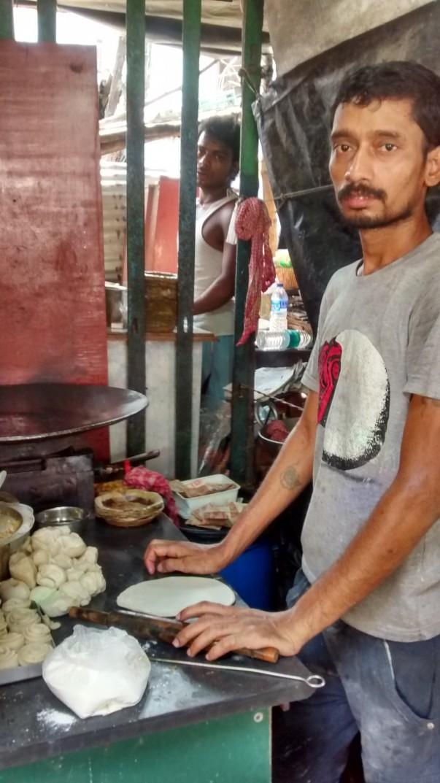 A boy rolls out dough to make a 'kochuri'i
